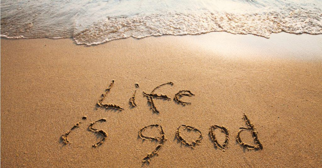 "Photo of a beach at sunset with ""Life is good"" written in the sand."
