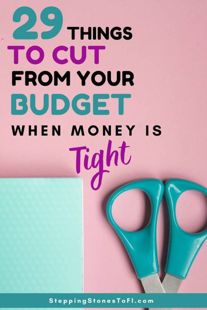 """Long Pinterest pin image of scissors on a desk with a notebook and text """"29 things to cut from your budget when money is tight"""""""