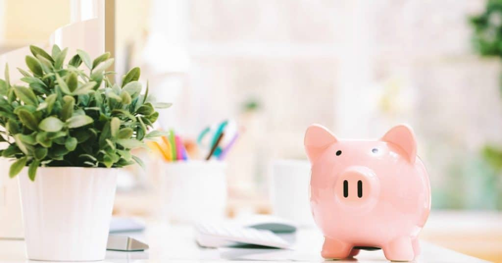 Piggy bank sitting on bright office desk, representing how to achieve financial security