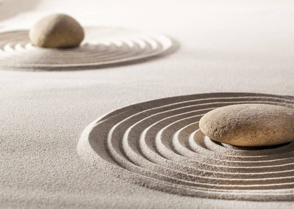 stones or pebbles in the middle of pure waves in sand for concept of tranquillity or wellbeing