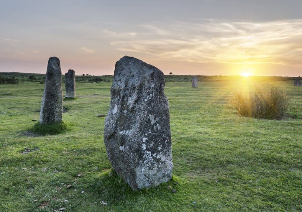 Standing stones in field at sunset, representing a Standing Stone Goal, a mid-range goal supporting a bigger long-range goal.
