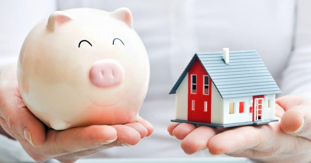 Image of a woman holding a piggy bank and a small model of a home. Which is better, a 15-year or a 30-year mortgage?