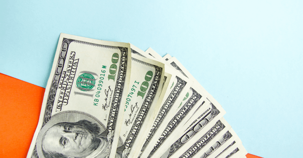 $100 bills splayed out on blue and orange background - How long to become a millionaire
