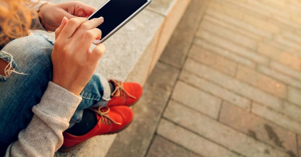 Woman using her smart phone to automate savings