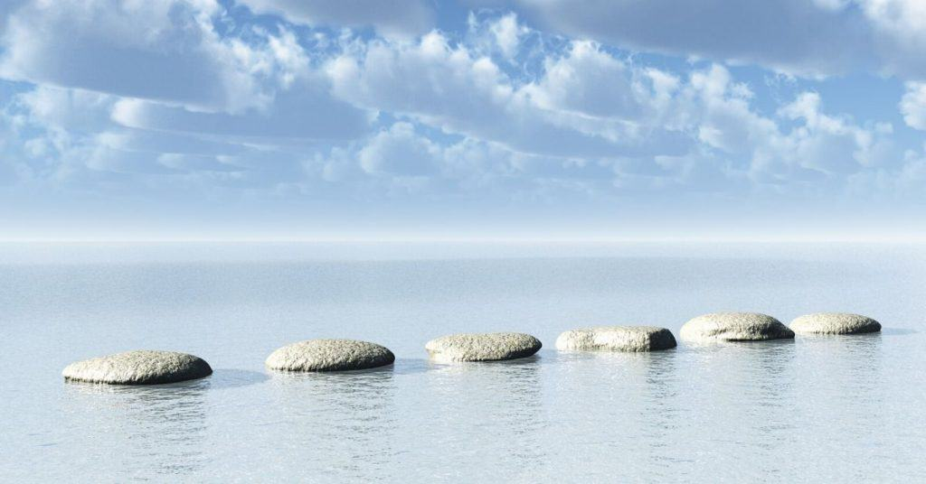 Stepping stones on blue sandy ocean beach