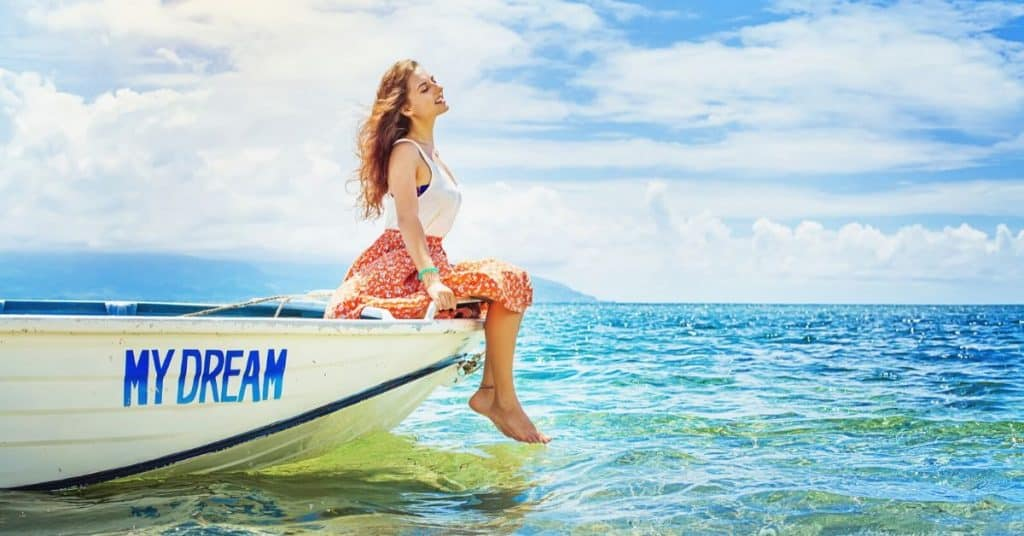 "Beautiful woman sitting on edge of a boat named ""My Dream"" in beautiful blue ocean water - Setting 10-Year goals to live your dream life."