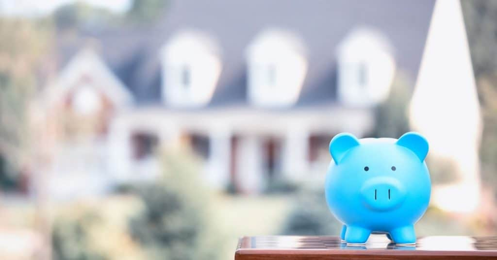 Blue piggy bank sitting in front of large home.