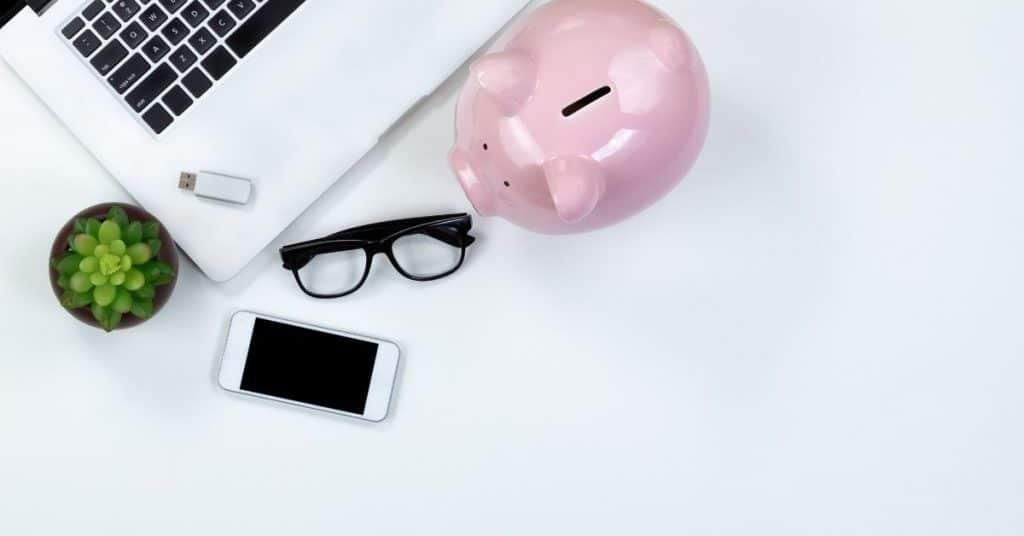 Piggy bank on desk top near computer and phone - Financial Goals
