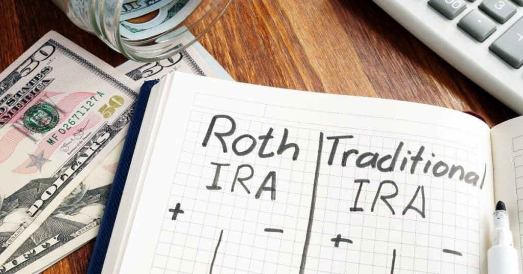 Open notebook with plus and minus columns for Roth vs. Traditional IRA's