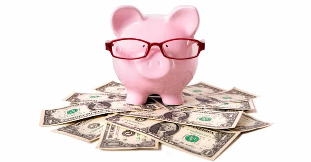 Piggy bank with glasses sitting on top of cash