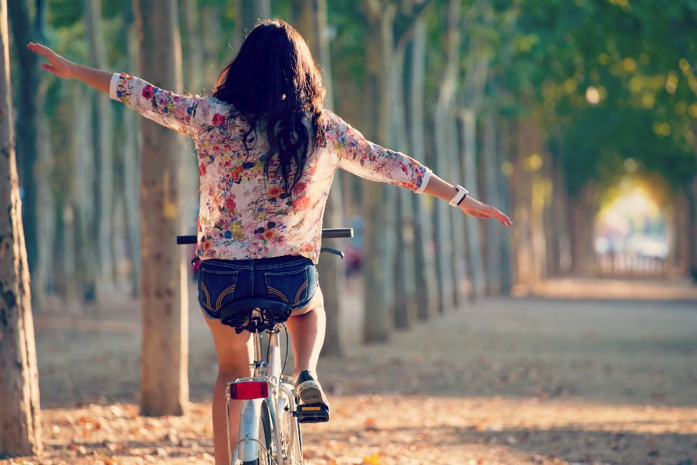 Girl riding bike down path of trees