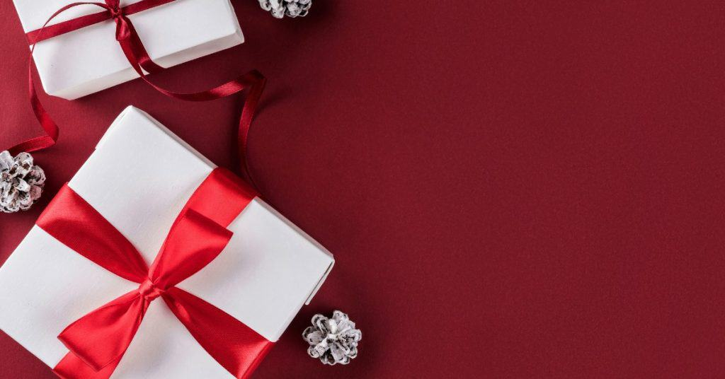 Presents with red ribbon against a red background, the 2019 gift guide for the financially savvy giver.