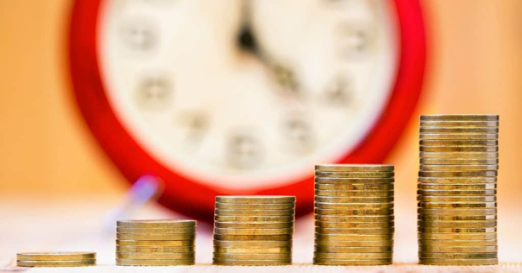 """Image of a clock in the background and increasing stacks of coins, text overlay """"Real-World Examples on the Power of Compounding Interest"""""""