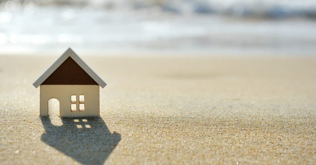 Toy house on the sand with waves in the background - on how to retire early with real estate investing