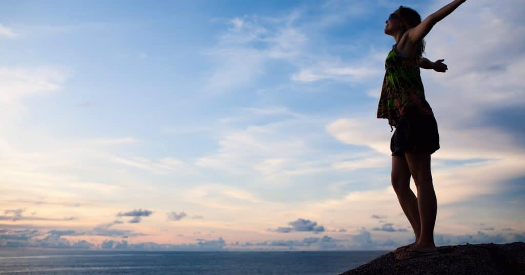 Joyful woman with arms outstretched overlooking beautiful vista