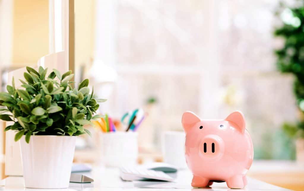 Pink piggy bank on a desk in an office