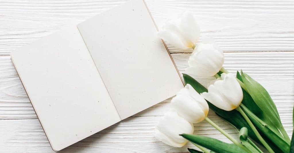blank planner open on white desk with tulips, represents using a goal setting planner