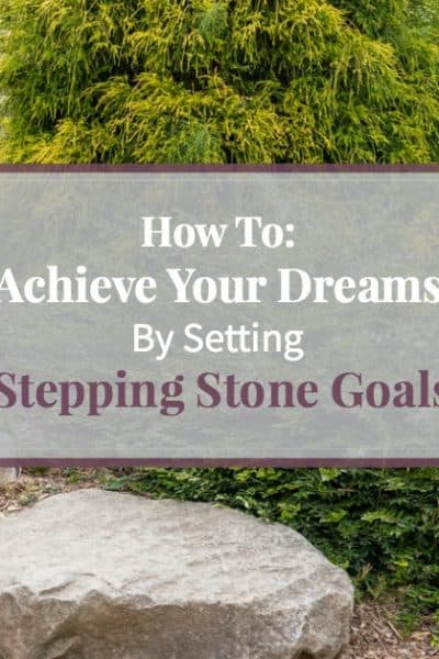 Image of large stone blocks forming a pathway up a hill in a Japanese garden, representing the stepping stone goals you need to set in order to achieve a bigger long-term goal.