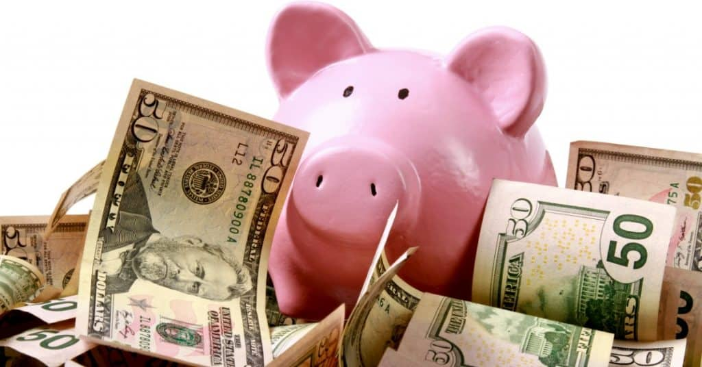 Pink piggy bank sitting on top of $50 dollar bills - tips to save more money