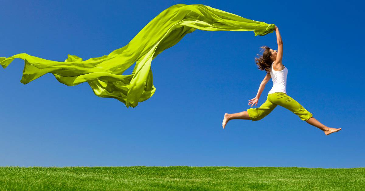 Woman leaping in the air with long green fabric flowing behind her, representing freedom and joy for achieving financial goals