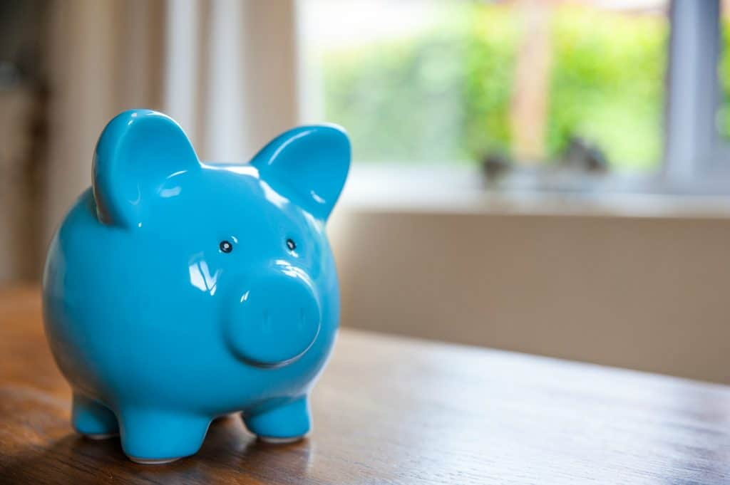 blue piggy bank on a wooden table in a house