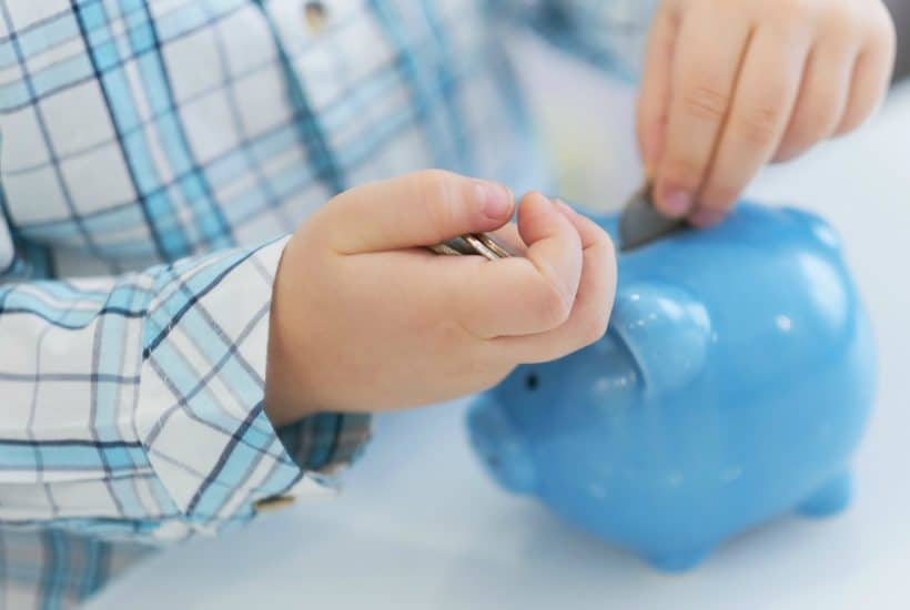 small boy placing coins in blue piggy bank
