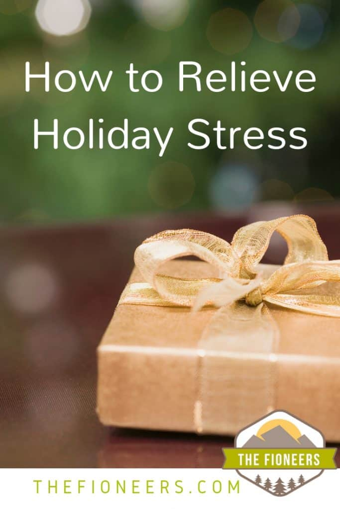 "Close up of a gift wrapped in gold paper with gold ribbon and text ""How to relieve holiday stress"""