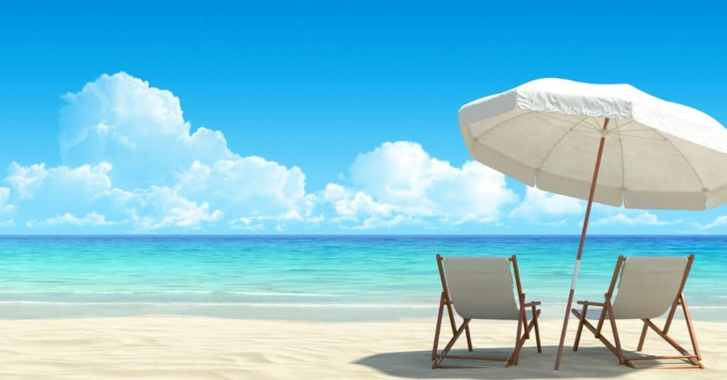 To lawn chairs with umbrella overlooking beautiful blue ocean - 9 Steps to Become a Millionaire