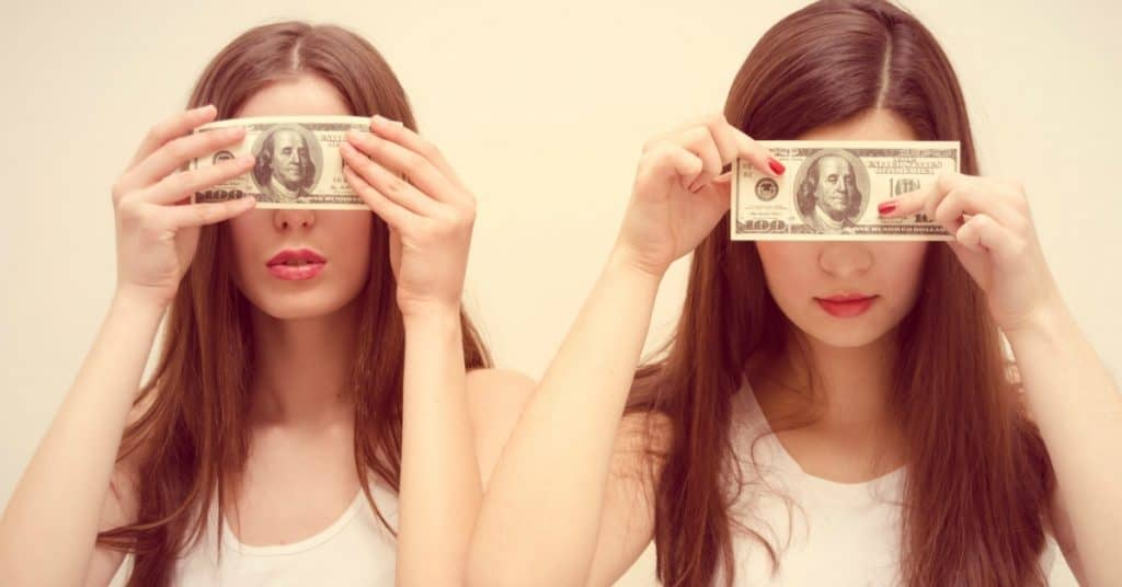 "Two young women holding $100 bills over their eyes with text overlay ""Self limiting beliefs about money - and how to overcome them"""