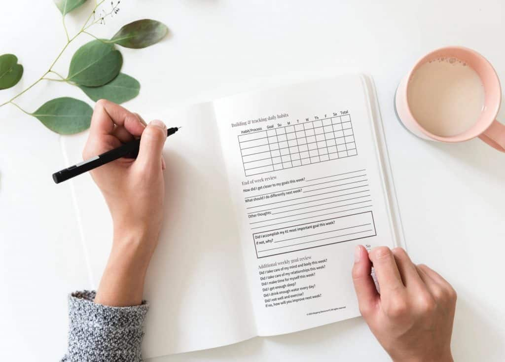 Desktop view of a woman writing in a 30-Day Goal Setting Planner