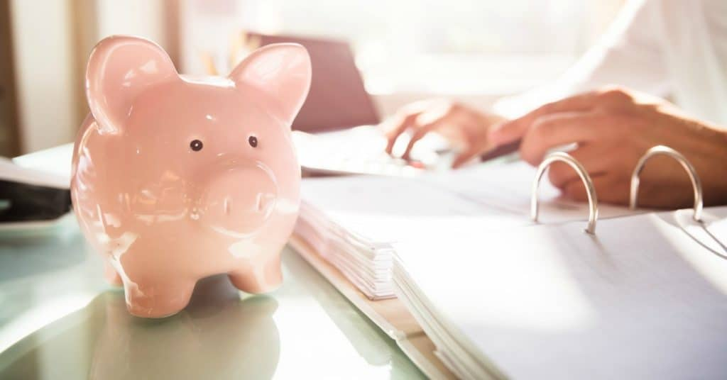 Piggy bank on desk with woman working on business paperwork, representing what to do when you are bad with money