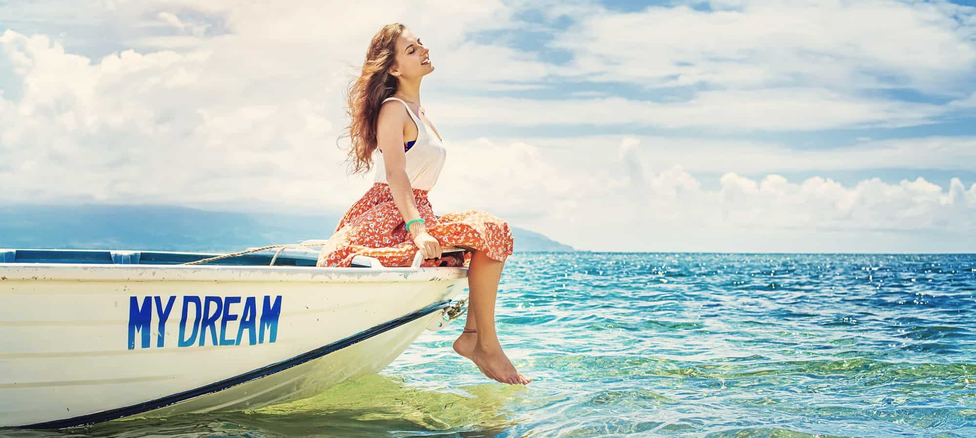 "woman sitting on edge of boat named ""MY DREAM"" representing goal setting and dreaming of the future"